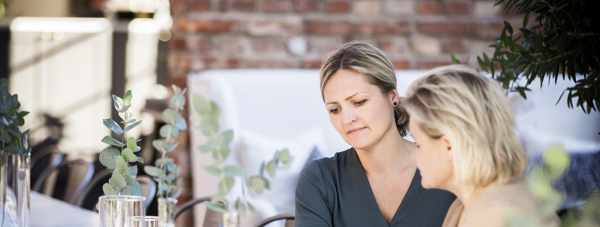 Två kvinnor vid ett bord tittar på gemensamma anteckningar
