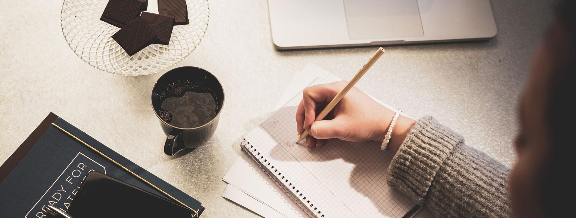 Hand med penna som skriver i ett block