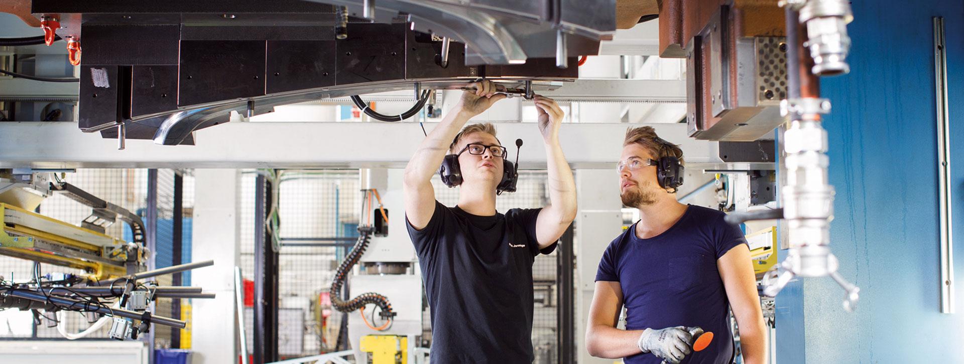 Två killar med hörselkåpor i arbete