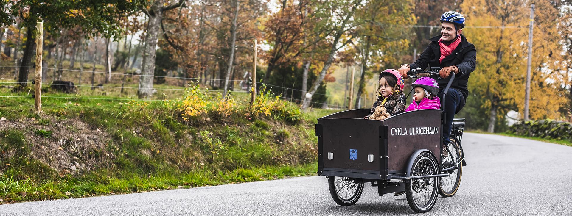 En man som cyklar med två barn i en cykelkärra