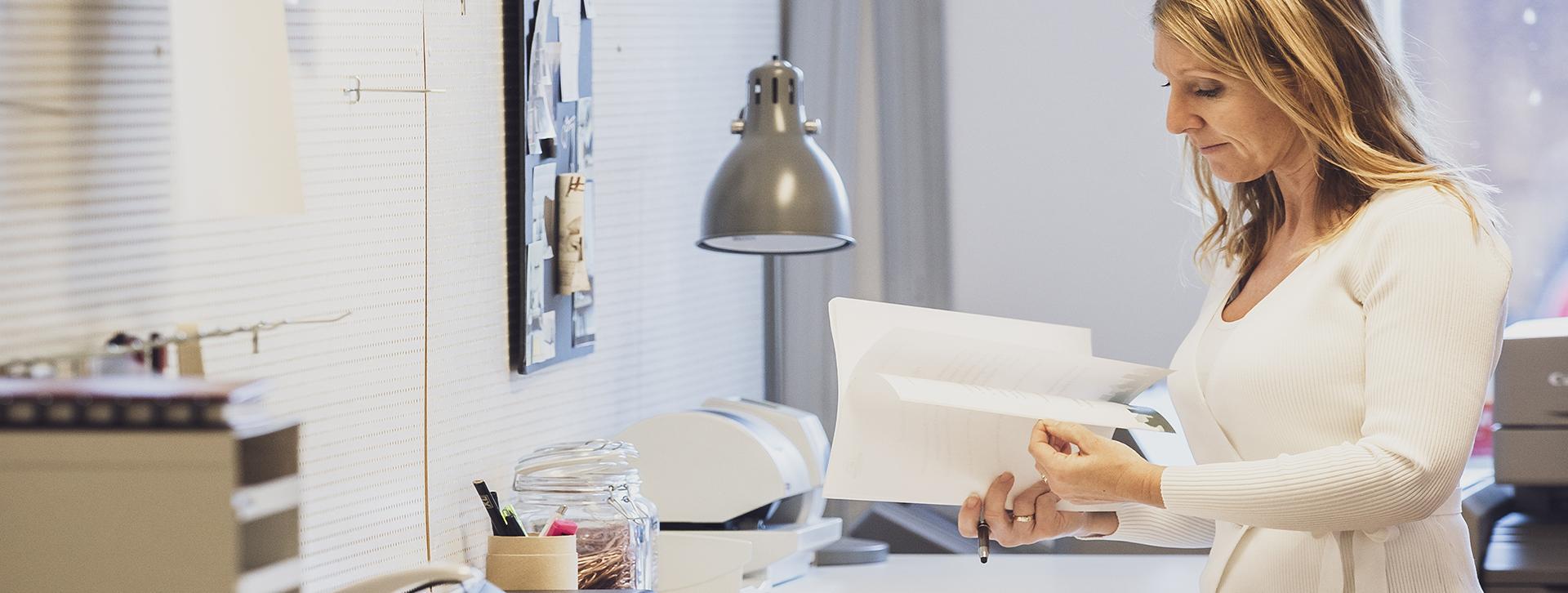 Näringsliv - Kvinna som bläddrar och tittar i papper, på kontoret