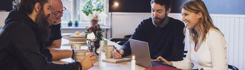 Att vara företagare - Fyra personer som arbetar tillsammans vid ett bord