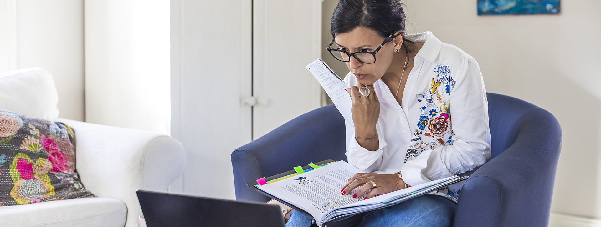 Starta företag - Kvinna sitter i fåtölj med en pärm och dator